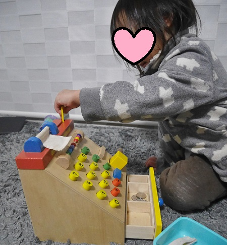 木製のレジスターで遊ぶ女の子