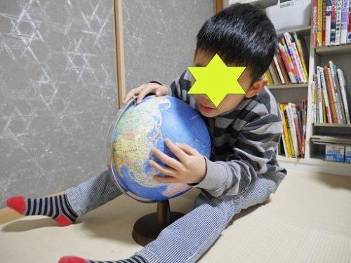 地球儀で日本を探す小学生の男の子