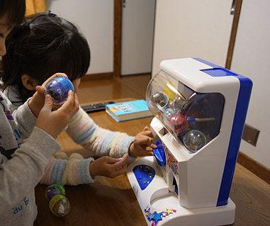家のガシャマシンで遊ぶ子供たち