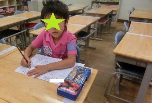 学校の教室で筆箱を使う小学1年生