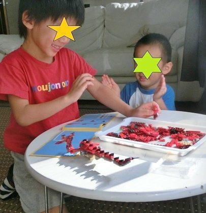 赤いさそりのレゴを作る男の子