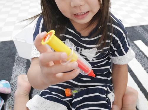 お医者さんごっこの注射で遊ぶ4歳の女の子
