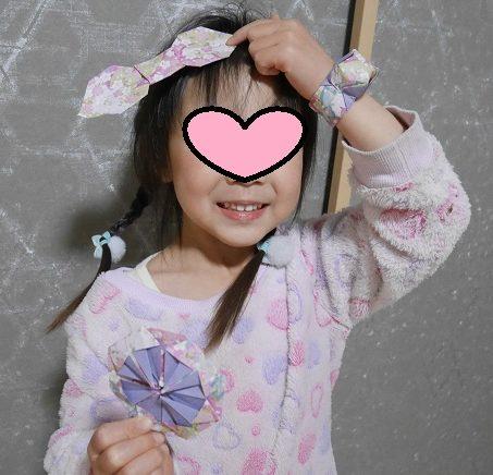 折り紙でダリアやリボン、腕時計を作る5歳の女の子