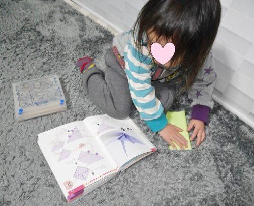 折り紙の本を見ながら鶴を折る女の子