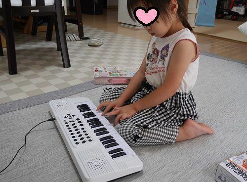 電子ピアノで弾く真似をしている4歳女の子