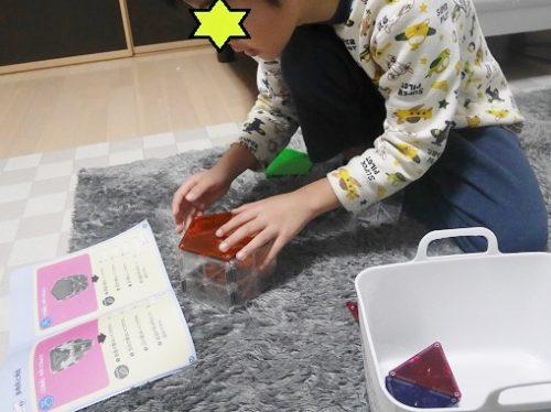 ピタゴラスのマグネットで、テキストを見ながら作る男の子