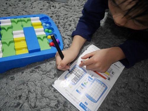 くもんのロジカルルートパズルの問題集を解く男の子