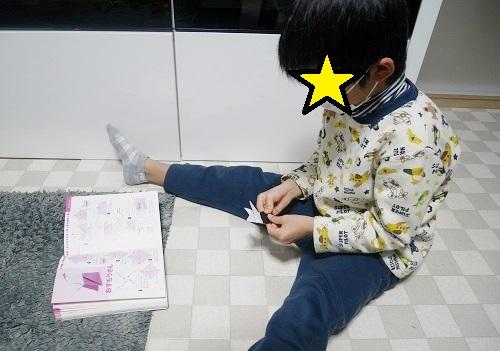 折り紙でとんとん相撲で遊ぶ男子