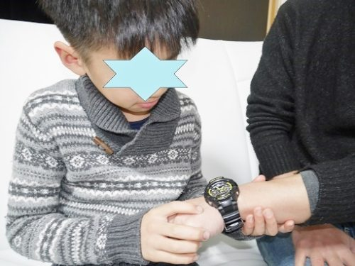 大人の腕時計を見つめる男の子