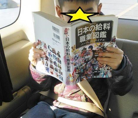 車の中で職業・給料図鑑を見る小学生