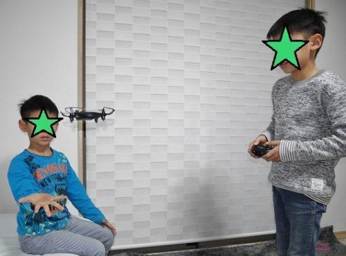 小型ドローンで室内で遊ぶ小学生の兄弟