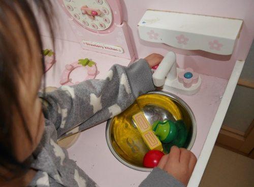 マザーガーデンのキッチン台のシンクで野菜を洗っている女の子