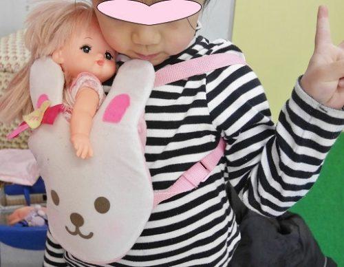 メルちゃんを抱っこひもで抱っこする女の子