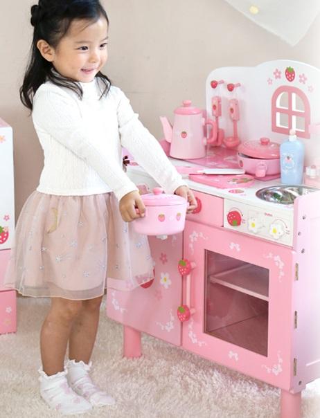 ピンクのおままごとキッチン台に立つ女の子