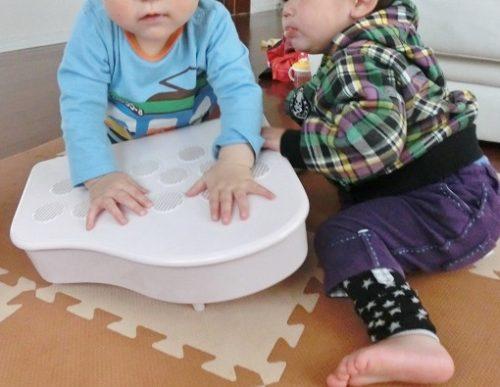 おもちゃのピアノの上に乗っかる子供