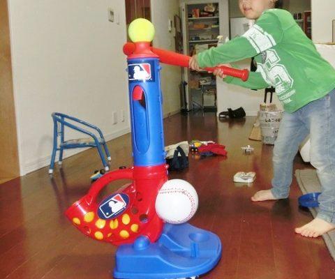 家の中で野球のバッティングマシーンで遊ぶ男の子