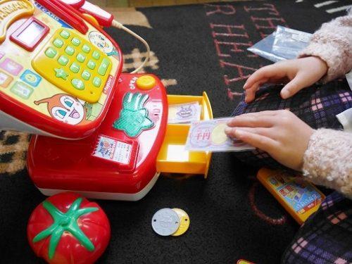 おもちゃのレジスターの引き出しにお金をしまう子供