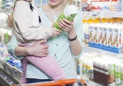 スーパーマーケットで母親が娘を抱っこしているところ