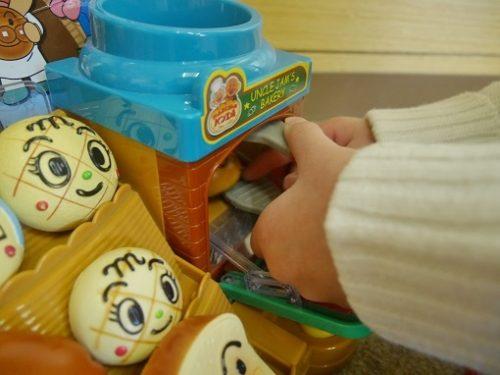 アンパンマンのパン屋のおもちゃでかまどにパンを入れる手