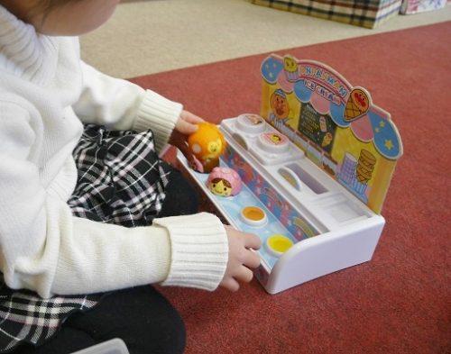アンパンマンのアイスクリームのおもちゃに商品を並べる女の子