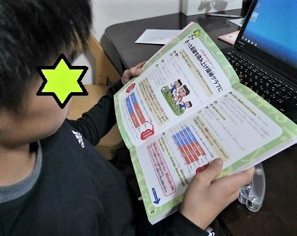 はじめての統計学図鑑を読む小学生の男の子