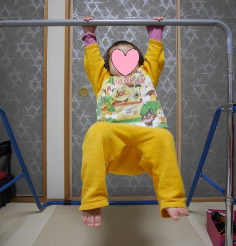 室内用鉄棒にぶら下がる1歳の女の子