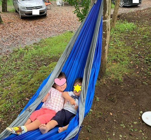 キャンプ場でハンモックで揺れている4歳と2歳の子供