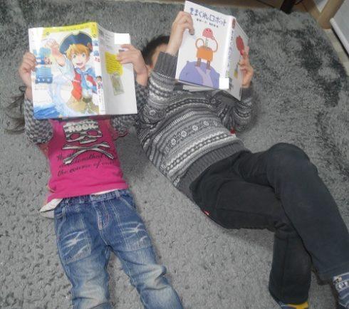 リビングで寝転がって読書をする子供2人