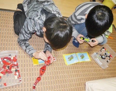 レゴのさそりと車を作る男の子2人