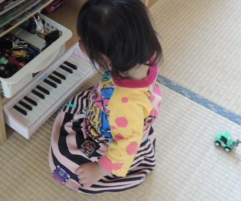 ピアノのおもちゃで遊ぶ女の子の後姿