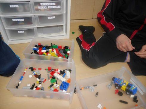 レゴの引き出しを床に置いて組み立てる男の子