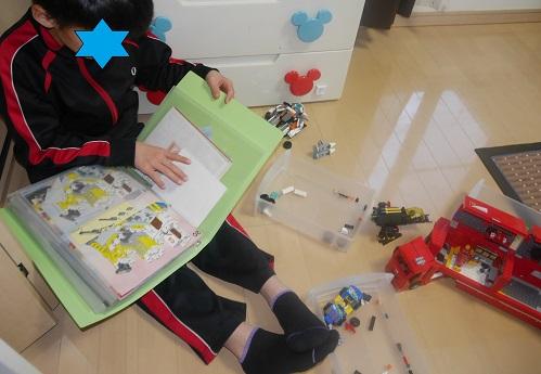 取説ファイルをめくってレゴの説明書を探す男の子