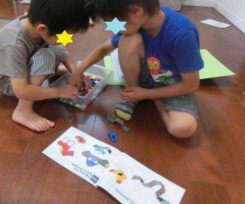 5歳と3歳の男の子がレゴを片付けているところ