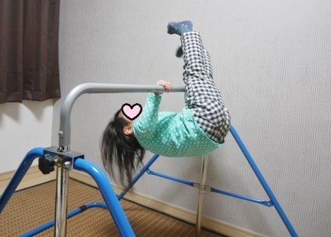 室内用鉄棒で逆上がりの練習をする3歳女の子