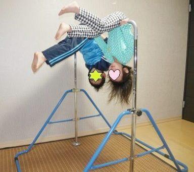 室内用鉄棒でおふとんの技を練習する子供