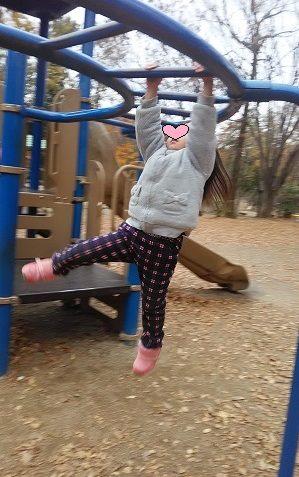 公園で雲梯をする3歳女の子