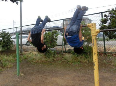 公園の鉄棒で逆上がりをする5歳と4歳の兄弟