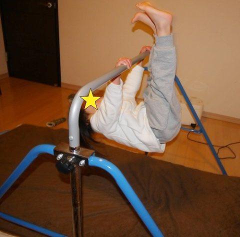 室内用鉄棒で逆上がりの練習をする子供