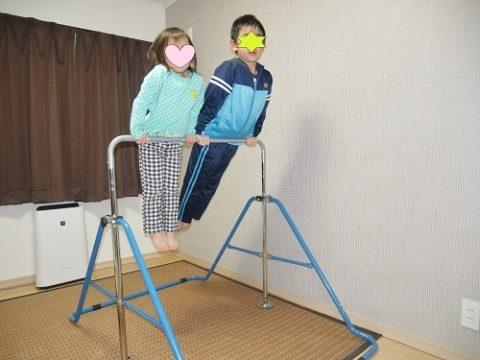 室内用鉄棒で遊ぶ4歳と小学生