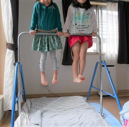 友達と一緒に室内用鉄棒で遊んでいる4歳女の子