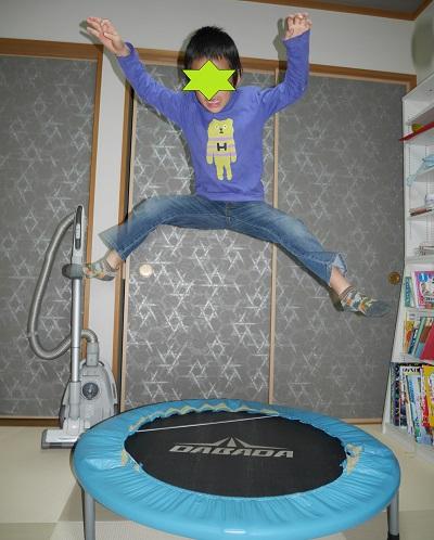 トランポリンで高く跳んでいる小学生男の子