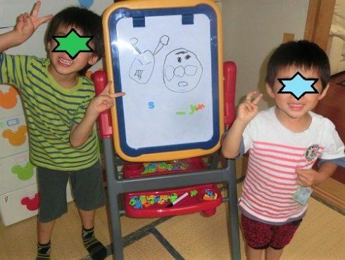 ホワイトボードや黒板のおもちゃで遊ぶ男の子