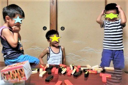 ジェンガで遊ぶ6歳と5歳の子供たち3人
