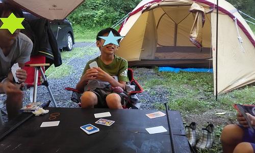 キャンプ場でボードゲーム「ハゲタカのえじき」をする家族