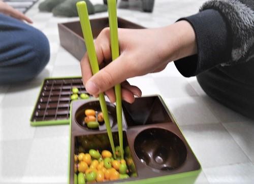 マナー豆匠で箸の練習をしている子供