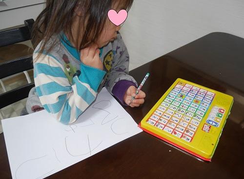 字の練習をしている3才の子供