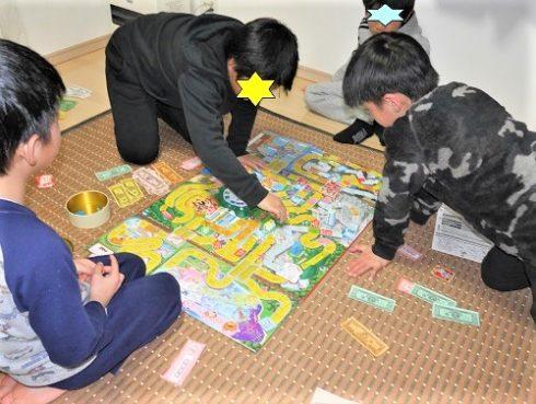人生ゲームで遊ぶ小学生低学年と高学年の男の子4人