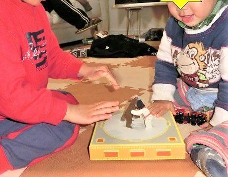 トントン紙相撲をして遊んでいる3歳と1歳の子供