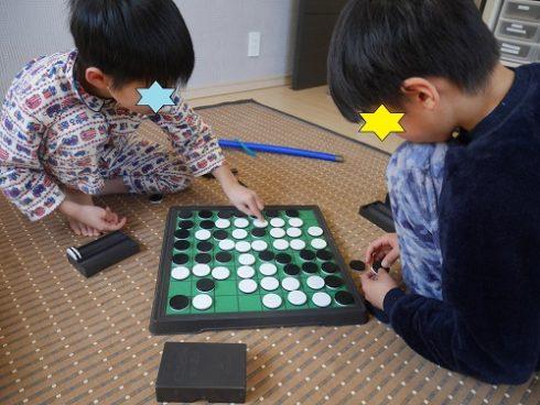 オセロで遊ぶ小学生の子供の兄弟