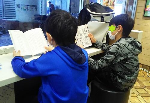 マクドナルドで読書をする小学生男の子